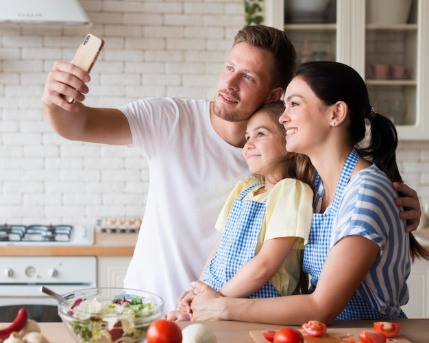 Glückliche familie, die selfie in der küche nimmt