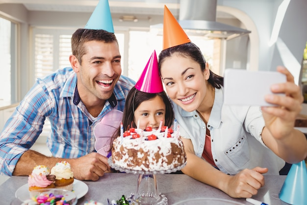 Glückliche familie, die selfie während der geburtstagsfeier nimmt