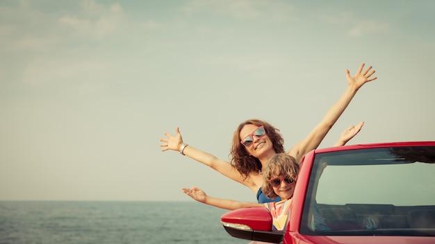 Glückliche familie, die sich am strand entspannt frau und kind, die spaß im roten cabriolet gegen blauen himmel haben sommerurlaub und reisekonzept