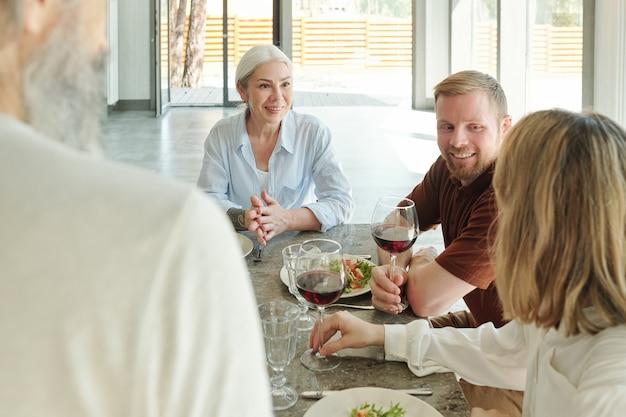Glückliche familie, die sich an einem tisch im elternhaus versammelt und letzte nachrichten über weinglas teilt