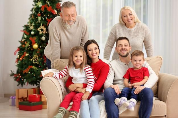 Glückliche familie, die sich im weihnachtlich dekorierten zimmer ausruht