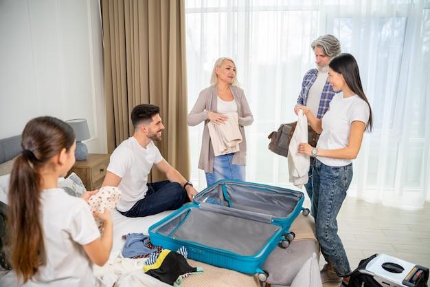 Glückliche familie, die sich zu hause auf eine reise oder einen urlaub im schlafzimmer vorbereitet. reisekonzept