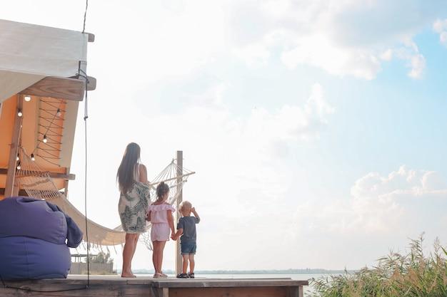 Glückliche familie, die sommerruhe durch glamping-haus in natürlicher umgebung genießt