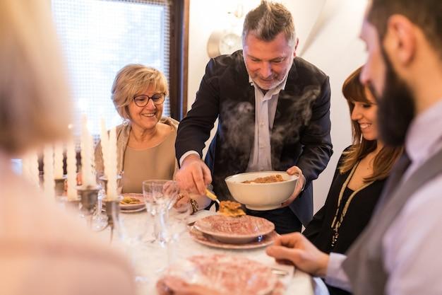 Glückliche familie, die sonntag zusammen zu hause zu mittag isst