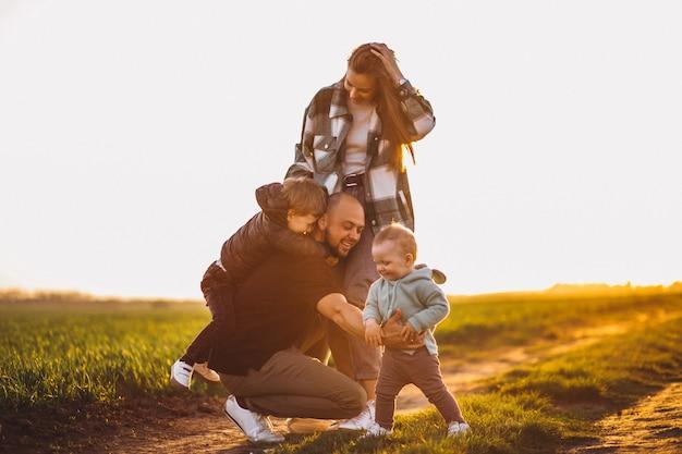 Glückliche familie, die spaß auf dem feld am sonnenuntergang hat