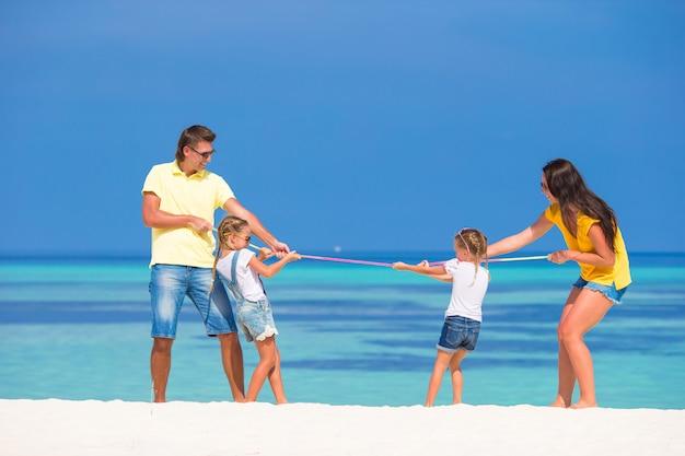 Glückliche familie, die spaß auf weißem strand hat