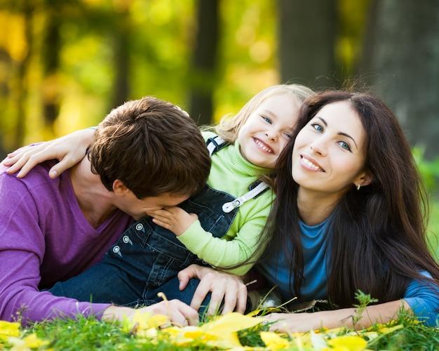 Glückliche familie, die spaß gegen unscharfen herbstlaubhintergrund hat