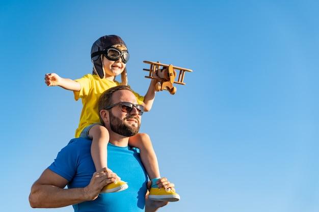 Glückliche familie, die spaß im freien hat. vater und sohn spielen gegen blauen sommerhimmelhintergrund.