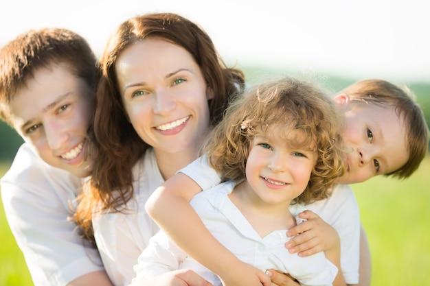 Glückliche familie, die spaß im freien im frühlingsfeld vor natürlichem grünem hintergrund hat