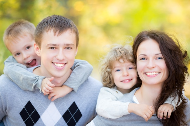 Glückliche familie, die spaß im freien im herbstpark gegen unscharfen blätterhintergrund hat