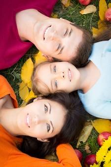 Glückliche familie, die spaß im freien im herbstpark hat. porträt von oben
