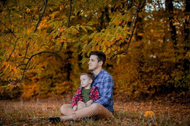 Glückliche familie, die spaß im freien im herbstpark hat. vater und sohn gegen gelb verschwommene blätter