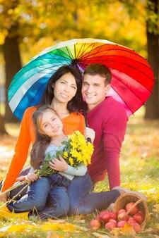 Glückliche familie, die spaß im freien im herbstpark hat