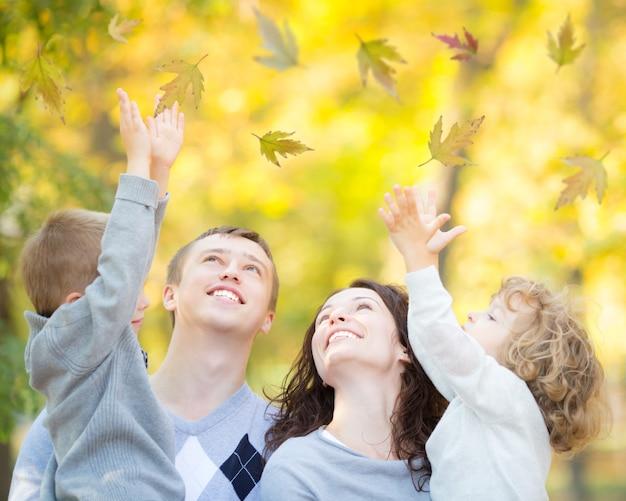 Glückliche familie, die spaß im freien im herbstpark vor goldenem sonnigem hintergrund hat