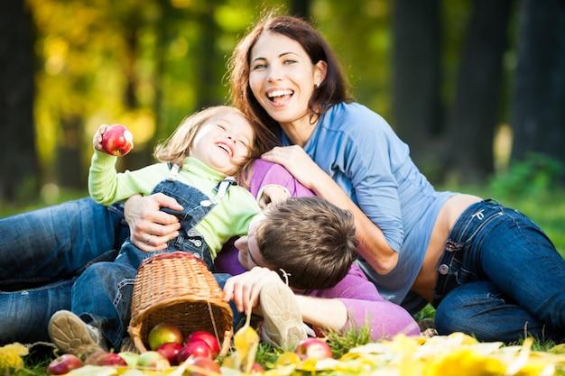 Glückliche familie, die spaß im herbstpark hat. fokus auf den menschen