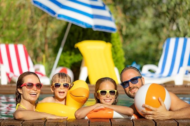 Glückliche familie, die spaß in den sommerferien hat. vater, mutter und kinder spielen im schwimmbad. aktives konzept für einen gesunden lebensstil