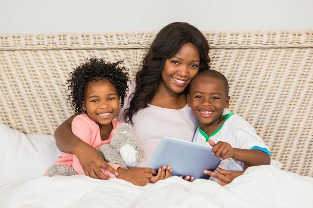 Glückliche familie, die tablette im bett verwendet