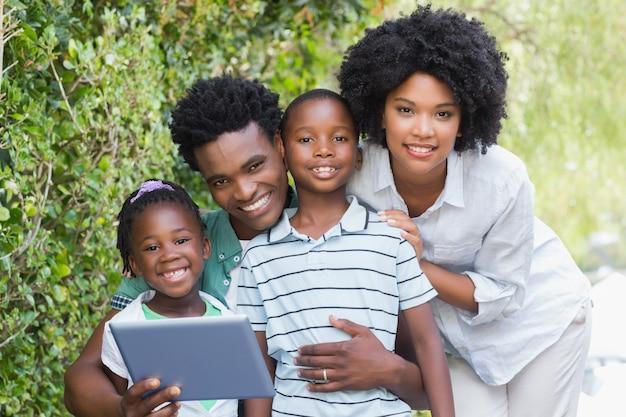 Glückliche familie, die tabletten-pc betrachtet