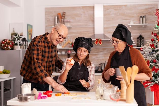 Glückliche familie, die traditionelles lebkuchendessert kocht, das teig macht