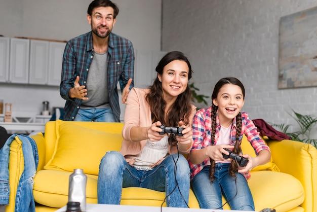 Glückliche familie, die videospiele im wohnzimmer spielt