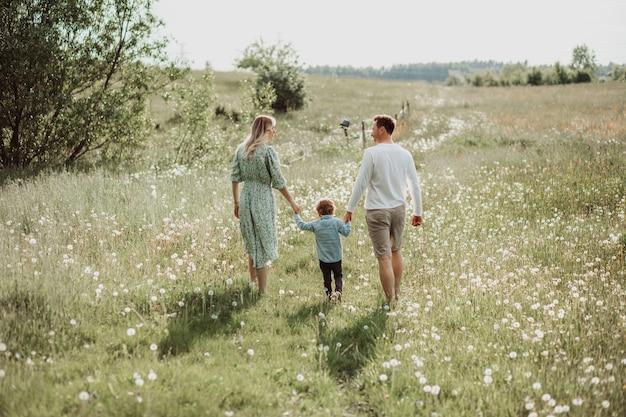 Glückliche familie, die von hinten im feld blühender blumen spaziert, papa, mutter und sohn, rückansichtsfoto