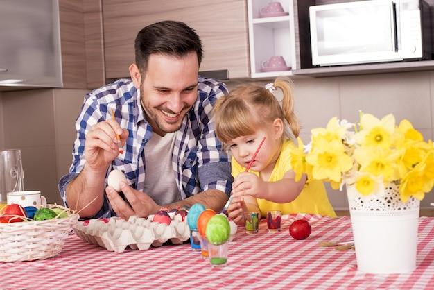 Glückliche familie, die vor freude ostereier bemalt