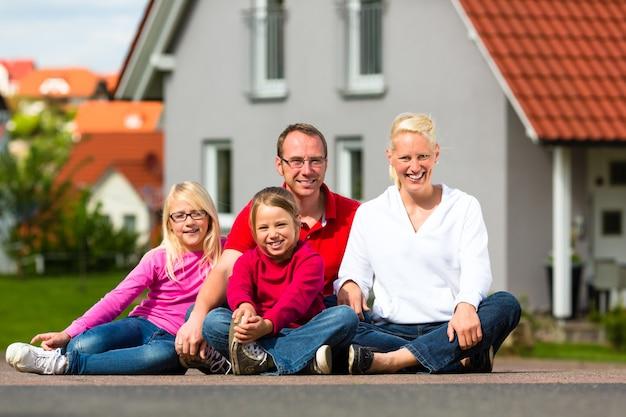 Glückliche familie, die vor haus sitzt