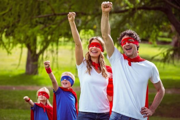 Glückliche familie, die vortäuscht, superheld zu sein