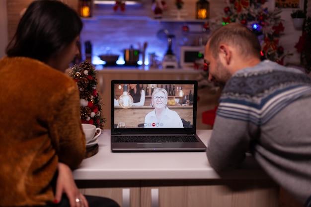 Glückliche familie, die während des online-videoanrufs mit entfernten großeltern diskutiert