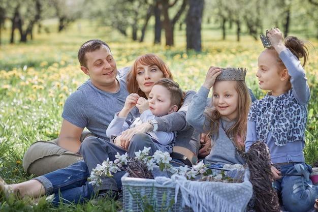 Glückliche familie, die während eines picknicks auf einer lichtung sitzt