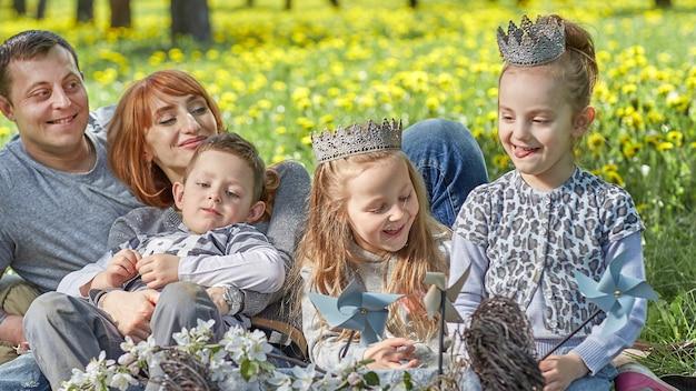 Glückliche familie, die während eines picknicks auf einer lichtung sitzt.