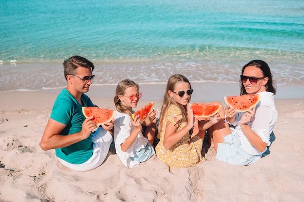 Glückliche familie, die wassermelone am strand isst