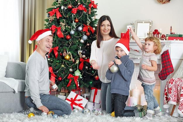 Glückliche familie, die weihnachtsbaum im feiertagswohnzimmer verziert