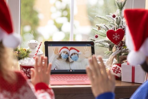 Glückliche familie, die weihnachtsferien online durch video-chat in quarantäne feiert. lockdown stay home-konzept. weihnachtsfeier während der pandemie coronavirus covid 19