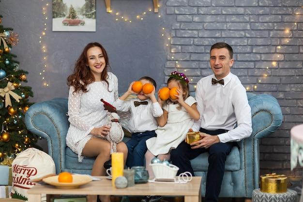 Glückliche familie, die weihnachtsgeschenk hält