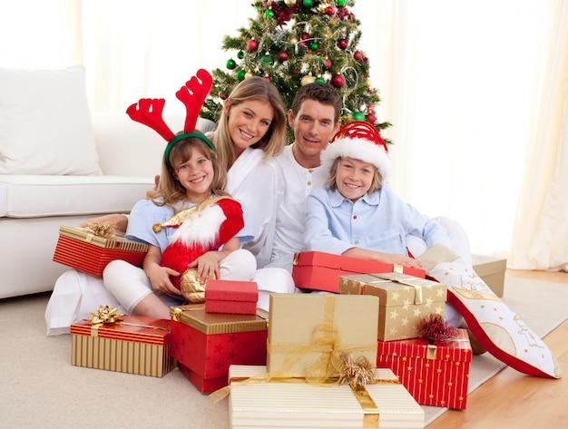 Glückliche familie, die weihnachtsgeschenke hält