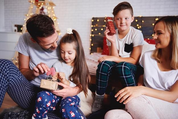 Glückliche familie, die weihnachtsgeschenke im bett öffnet