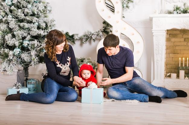 Glückliche familie, die weihnachtsgeschenke nahe weihnachtsbaum hält. baby, mutter und vater haben spaß zu hause