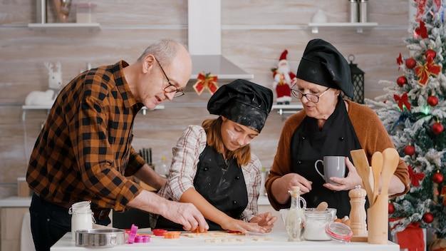 Glückliche familie, die weihnachtsköstliches lebkuchendessert mit keksform zubereitet