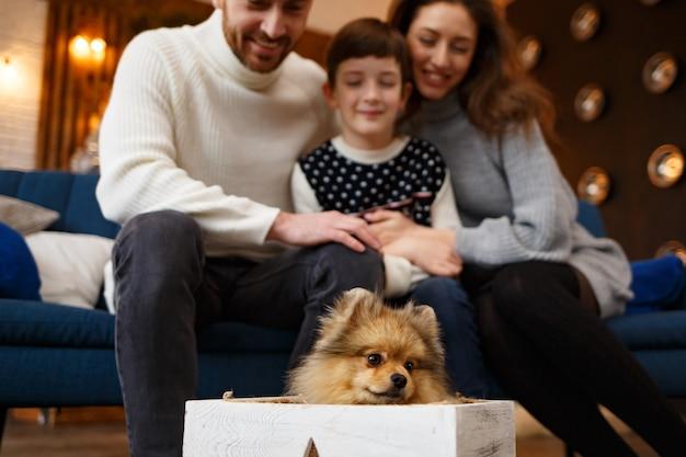 Glückliche familie, die weihnachtsmorgen zusammen verbringt