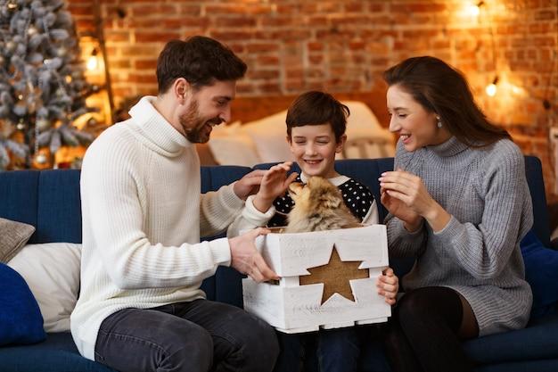 Glückliche familie, die weihnachtsmorgen zusammen winterferien-weihnachtsfeiern neujahrskonzept verbringt