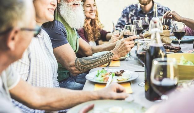 Glückliche familie, die wein beim grillabendessen auf der terrasse im freien isst und trinkt