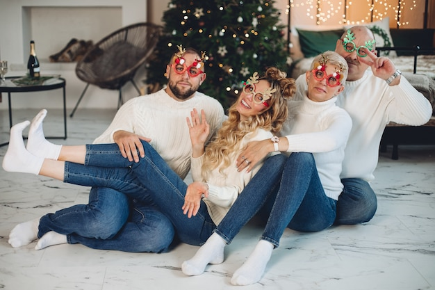 Glückliche familie, die weiße pullover trägt und spaß beim gemeinsamen feiern des neuen jahres hat