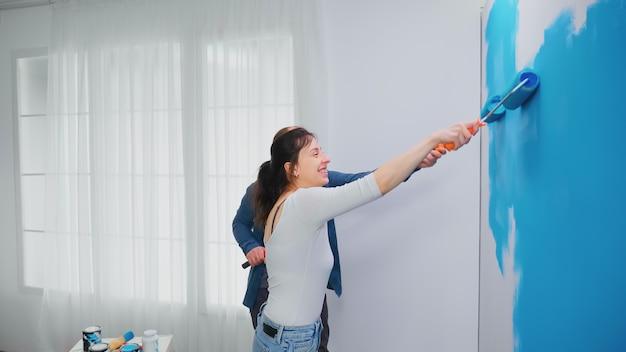 Glückliche familie, die wohnungswand mit blauer farbe mit rollenbürste malt. heimtextilien und renovierung in gemütlicher wohnung, reparatur und verjüngungskur