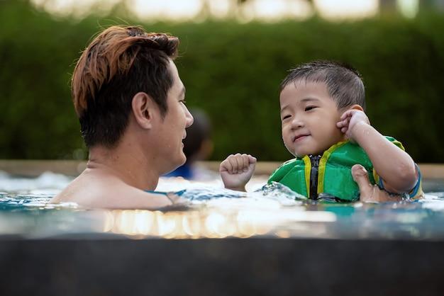 Glückliche familie, die zeit im pool an den sommerferien schwimmend genießt.