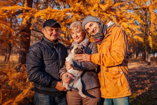 Glückliche familie, die zeit mit pughund im herbstpark verbringt eltern mit ihrem sohn, der haustier umarmt