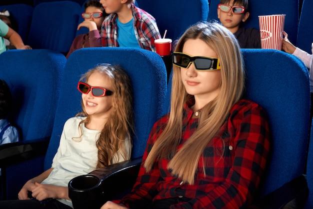 Glückliche familie, die zeit zusammen im kino verbringt. attraktive junge mutter und lachende kleine tochter, die 3d-brillen beim ansehen des films trägt
