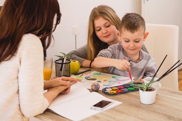 Glückliche familie, die zu hause malt