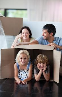 Glückliche familie, die zu hause mit kästen spielt