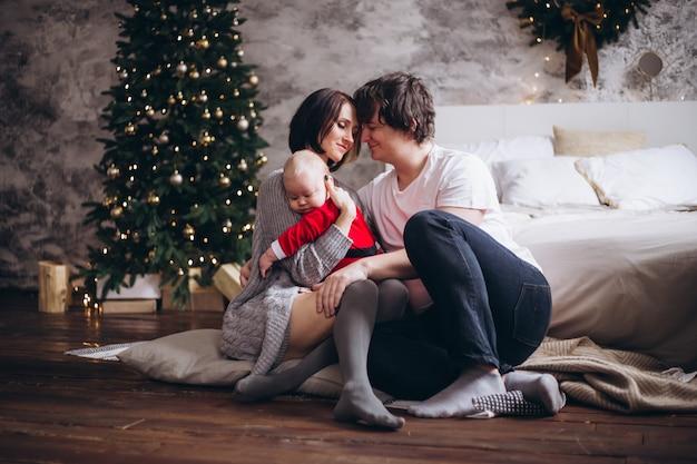 Glückliche familie, die zu hause über weihnachtsbaum umarmt